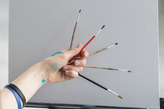 少女アーティストは、きれいなキャンバスに油絵の具でペイントするためのさまざまなブラシを保持しています。