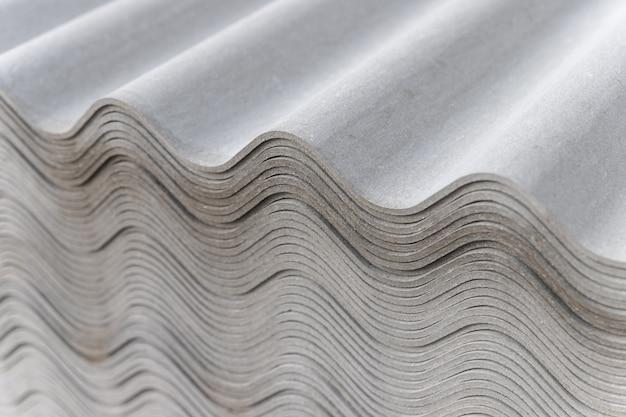 Многие серые шиферные листы сложены друг на друга. волнистые полосы