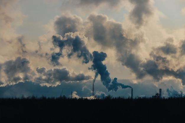 工場の煙突は、濃い煙で大気を汚染します。