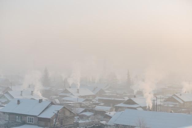 寒い冬の日。外は冷ややかです。煙突の煙の村の家。