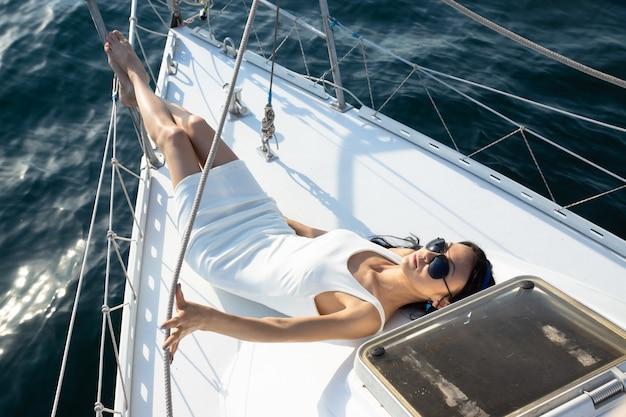 白いドレスを着た魅力的なファッションの女性は、ヨットのデッキに横たわっています。