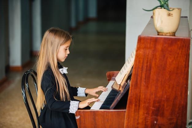 黒のドレスを着た少女はピアノを弾くことを学ぶ。子供は楽器を演奏します。
