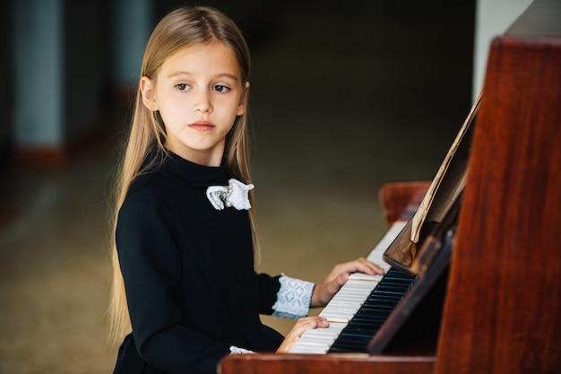 Маленькая девочка в черном платье учится играть на пианино. ребенок играет на музыкальном инструменте.