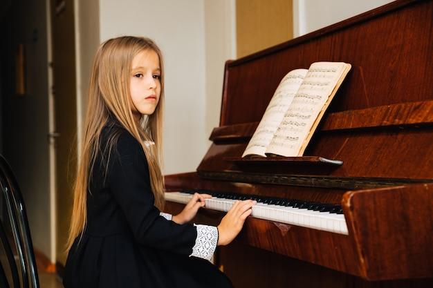 Маленькая девочка в черном платье учится играть на пианино. ребенок играет на музыкальном инструменте. школьница смотрит в сторону.