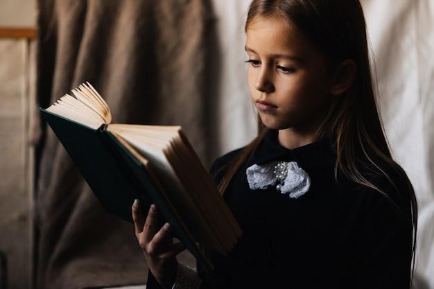 黒のドレスの少女は、緑の本を保持し、それを読みます。