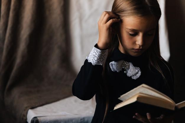 Маленькая девочка в черном платье держит зеленую книгу и читает ее.