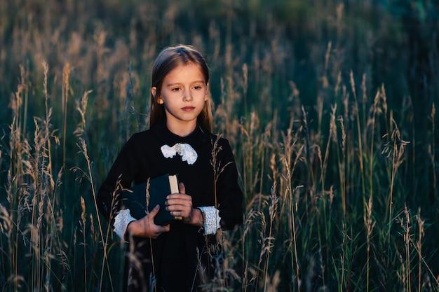 黒いドレスを着た少女が背の高い草の中に立って、夕日を見ながら緑の本を持っています。