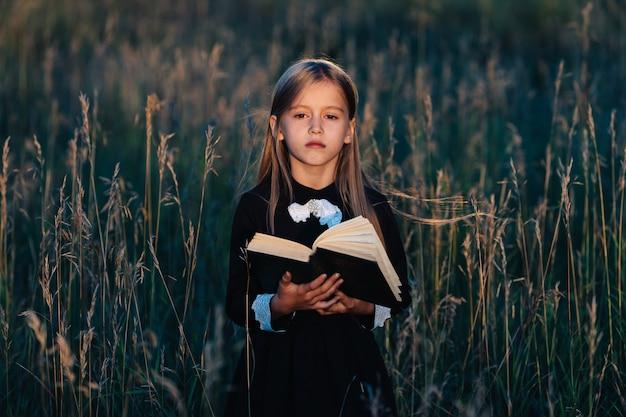 Маленькая девочка в черном платье стоит в высокой траве и держит зеленую книгу в свете заходящего солнца. ребенок с задумчивым выражением лица.