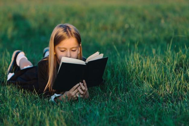 Ребенок лежит на траве и читает книгу в лучах заката.
