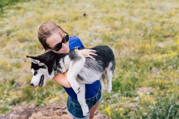 女性は彼女の腕の中で犬を保持しています。自然の中でハスキー。