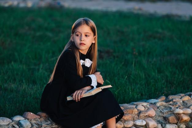 Ребенок сидит на каменном заборе и держит книгу, отворачиваясь и размышляя.
