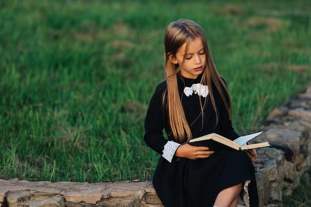 Ребенок сидит на каменной скамье и читает книгу.