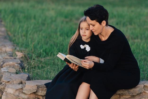Мать и дочь сидят на каменной скамейке и читают книгу. женщина с ребенком в черных платьях.