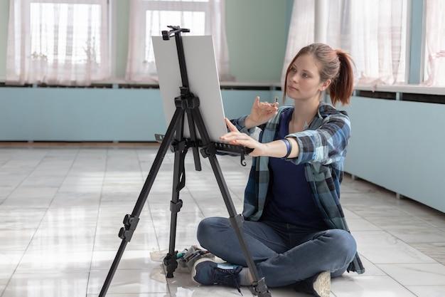 Молодой подросток женщина художник краски масляными красками, сидя на мраморном полу. белый холст и мольберт стоят на полу из мраморной плитки в комнате с бирюзовыми и светло-зелеными стенами.