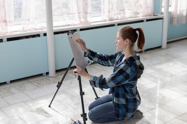 Молодой подросток женщина-художник сидит на полу из мраморной плитки. женщина в процессе покраски масляными красками.