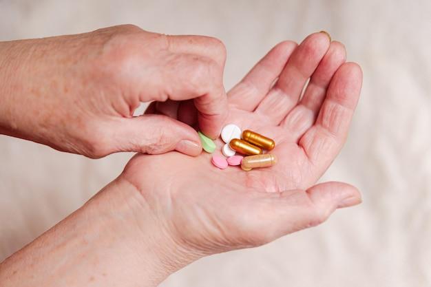 高齢者の手で多くの異なる薬。老人は彼の手の手のひらからピルを服用します。