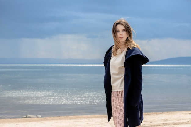 大人の美しい少女が、雨が近づいてくる雲を背景に海岸に立っています。