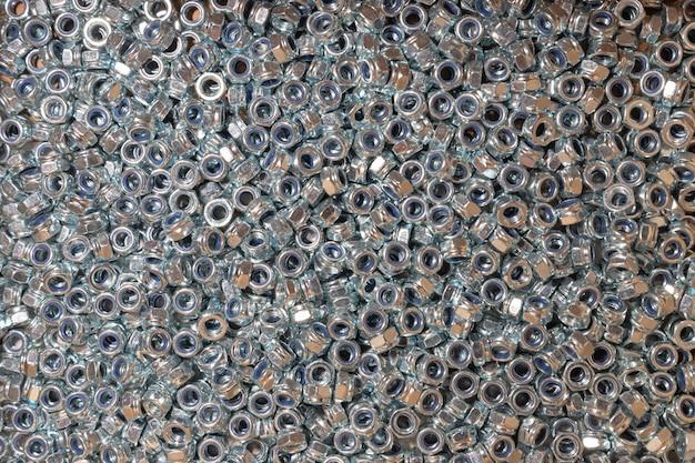ナッツ。テクスチャ。ボルトやネジ用のゴム引きナットがたくさん。壁紙の背景。