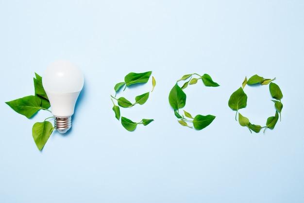 Светодиодная лампа с листьями на синем фоне. концепция зеленой энергии.