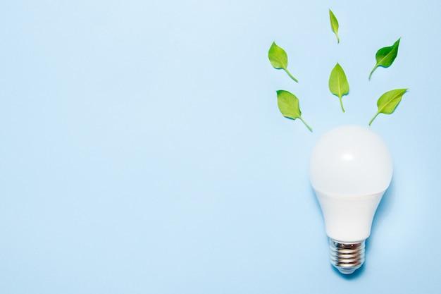 青色の背景に葉が付いている導かれたランプ。グリーンエネルギー効率の概念