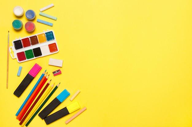 教育と学校のコンセプトに戻る黄色の背景上に描画するための学用品。平面図、平面レイアウト。
