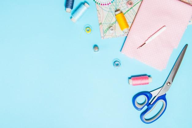 ミシン用品、パターンおよび青色の背景色、ステッチ、刺繍の裁縫用アクセサリー。テキスト用のスペース平干し、上面図。