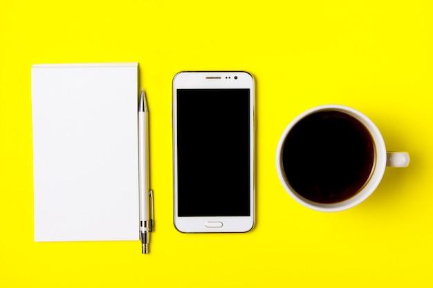 スマートフォン、メモ帳、黄色の背景に一杯のコーヒー