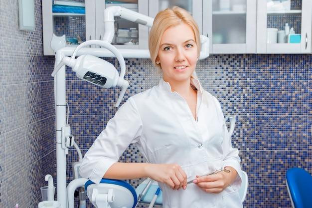 白い制服を着た女性歯科医は、歯科医院での歯科用機器のポーズ