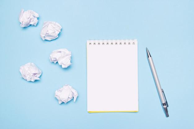 空のノートブック、ペン、青い紙の上に紙を丸めてボールを開く