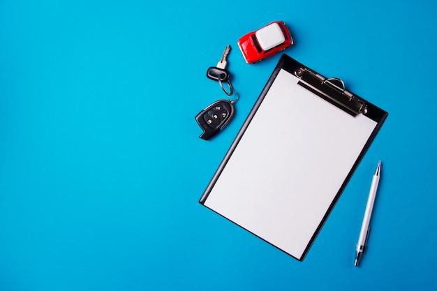 赤いおもちゃの車と青色の背景にキーを持つ空白の紙。技術検査または自動車クレジット