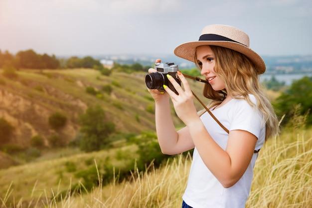 ビンテージカメラで若いかわいいブロンドの女性は、渓谷の自然の写真を撮る。旅行ブログと女性写真家