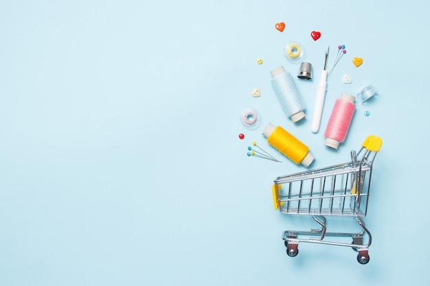 青色の背景、ステッチ、刺繍のミシンアクセサリーとスーパーマーケットのカート。