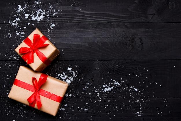 クリスマスの組成物。木製の黒い背景にクリスマスプレゼント。グリーティングカードの概念。トップビュー、フラットレイアウト、コピースペース。