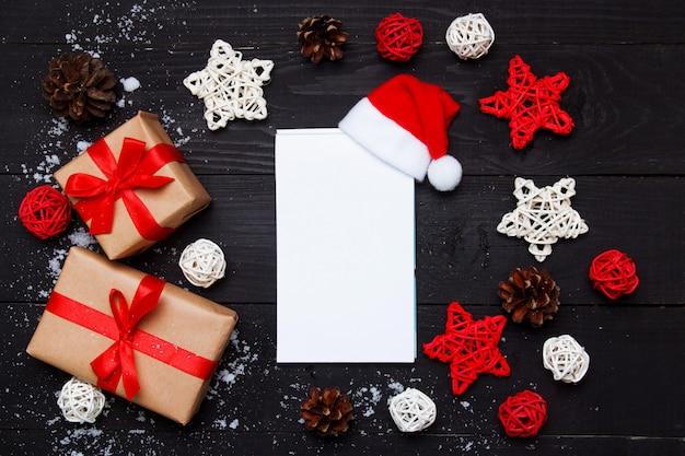 クリスマスの組成物。クリスマスプレゼントと木製の黒い背景に装飾が施されたメモ帳。トップビュー、フラットレイアウト、コピースペース。