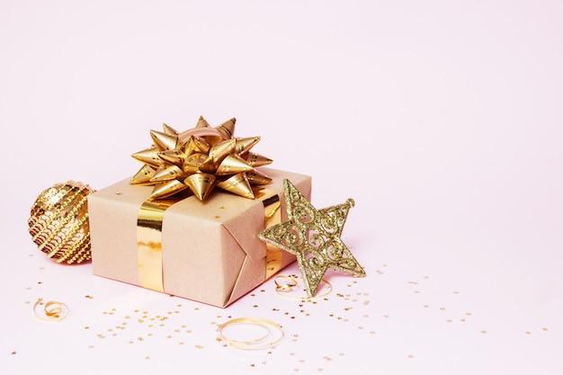 クリスマスのグリーティングカードの構成。ゴールデンボール、紙吹雪星、ピンクの背景の金の装飾とクラフトペーパーギフト