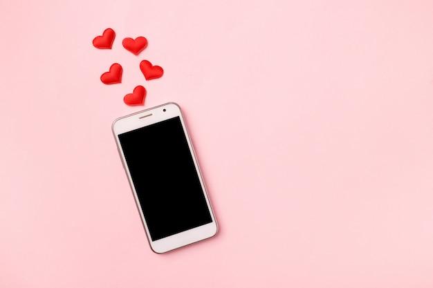 ピンクのパステル調の背景にモバイル携帯電話と赤いハートのトップビュー