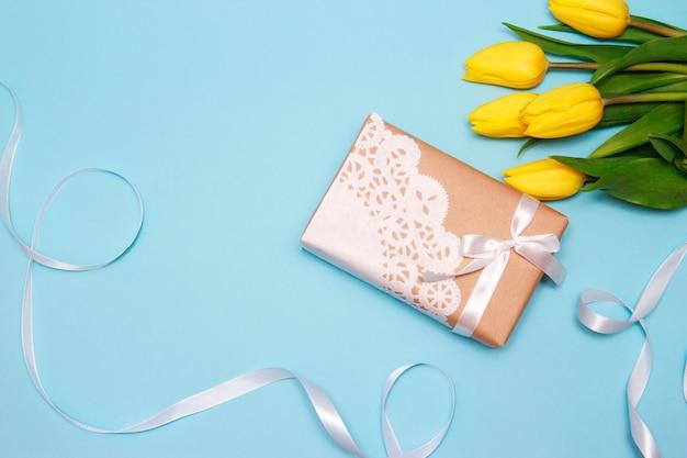 黄色いチューリップの花束とペーパークラフトの贈り物は、青い紙の背景にレースナプキンで飾られています。