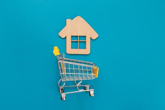 青のおもちゃの木造住宅のショッピングのための小さなスーパーマーケットのカート