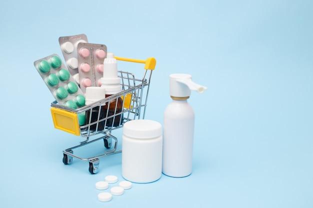 青色の背景にショッピングカートの薬と錠剤。ドラッグデリバリー。コピースペース