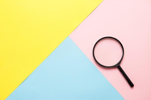 色紙の上の拡大鏡。上面図。検索の概念