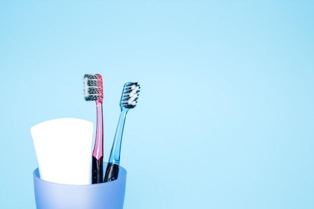 ガラス、青い背景の歯磨き粉と歯ブラシ。コピースペース