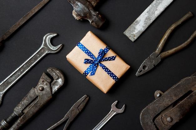 黒い紙の背景にヴィンテージの古いツールとギフトを作ります。父の日の概念。フラットレイ