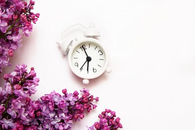 白い背景の上のビンテージの小さな目覚まし時計とライラックの花