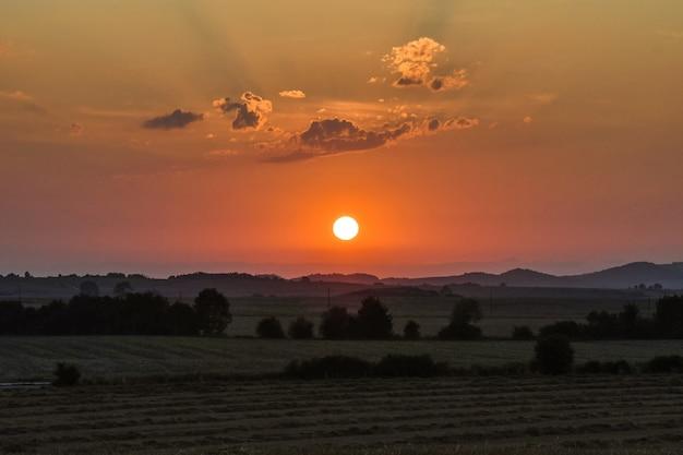バックグラウンドで美しい太陽とフィールドの夕日