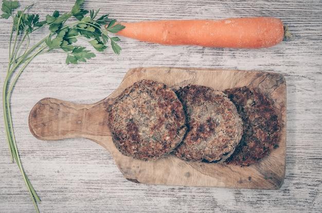 Вегетарианский бургер с чечевицей. вегетарианское блюдо здоровое. деревянный фон