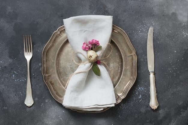 Пасхальный романтический ужин. сервировка стола элегантность с весенними розовыми цветами на темноте. вид сверху.