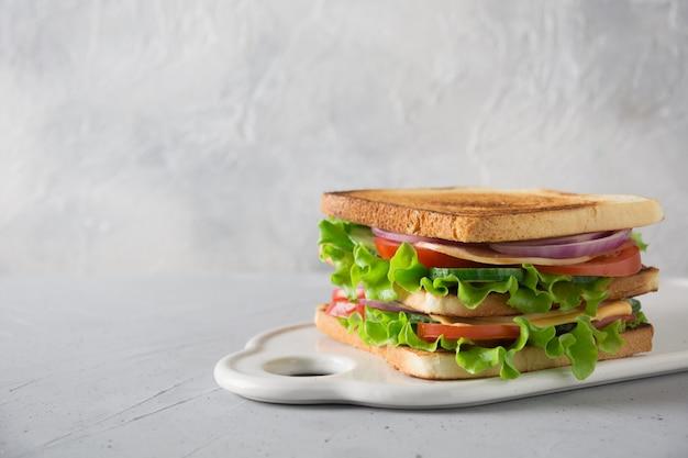 Сэндвич с белым тостом хлеб, бекон, помидор, лук, салат, сыр на белом.