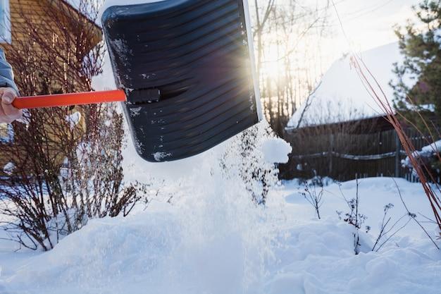 シャベルで雪をクリアする人