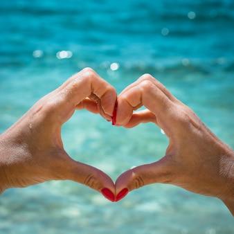 海を背景にハートの形の赤い爪を持つ女性の手。愛の概念
