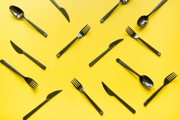 使い捨てピクニックブラックナイフとフォークの黄色。